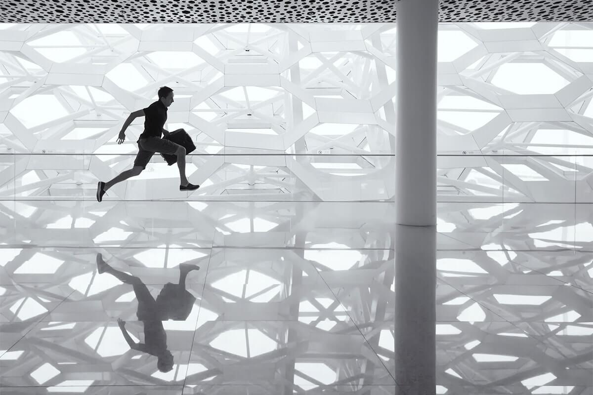 Een man met een tas in zijn handen springt in een expositiehal