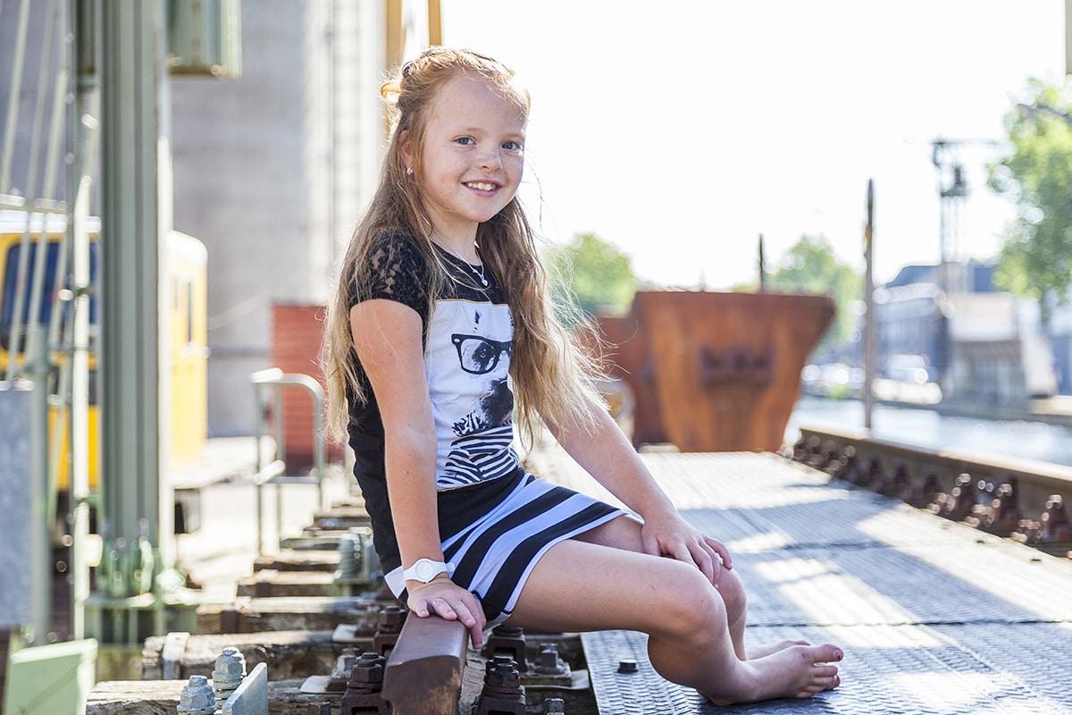 Jong meisje poseert zittend in de zon bij het koekgebouw in Veghel