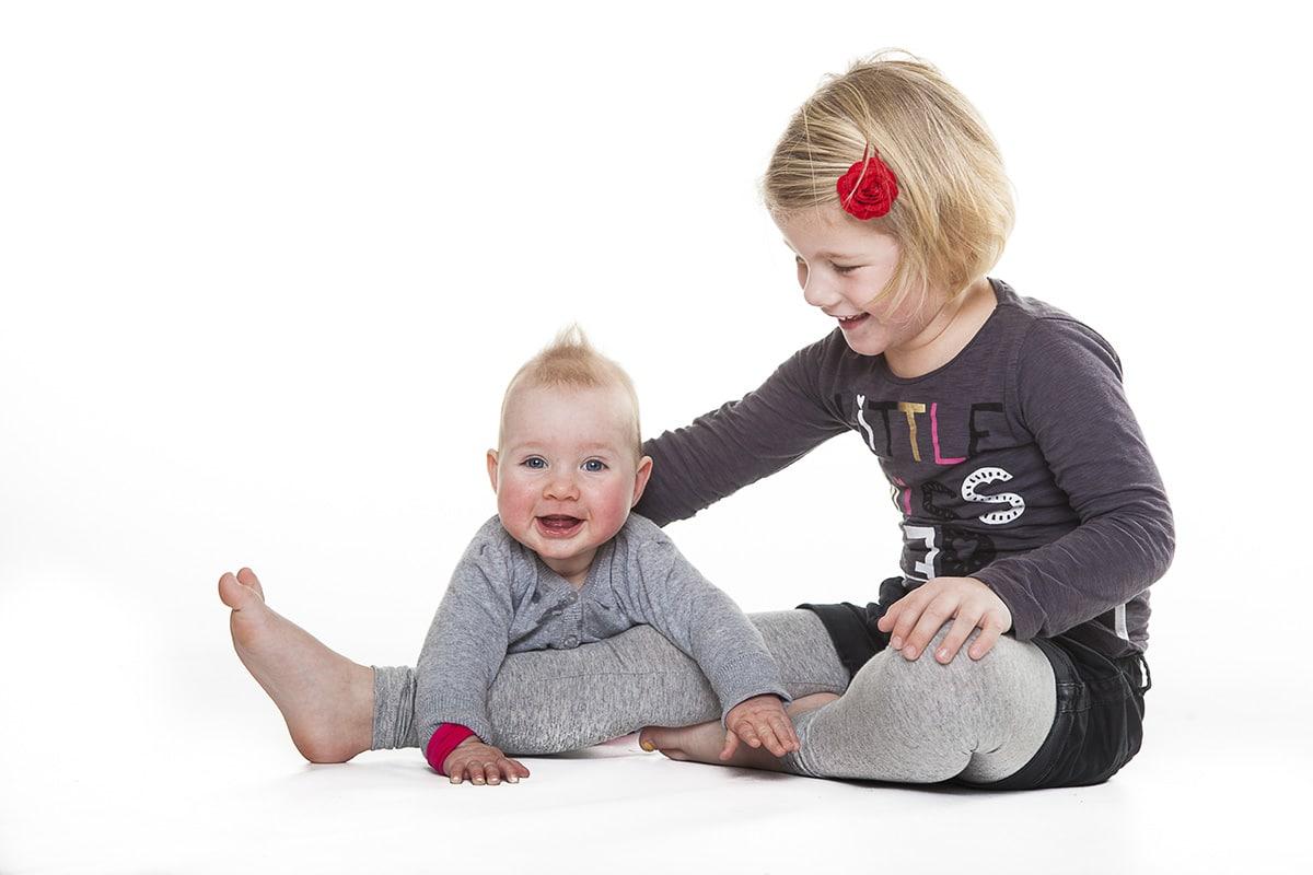 Twee meisjes poseren in de studio tijdens een fotoshoot.