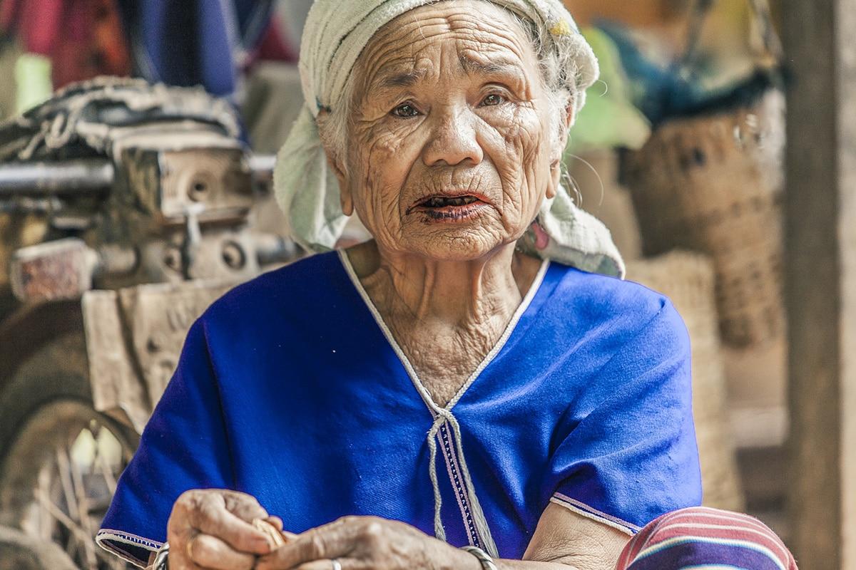 Oudere dame die op tabak aan het kouwen is in een hutje in Thailand