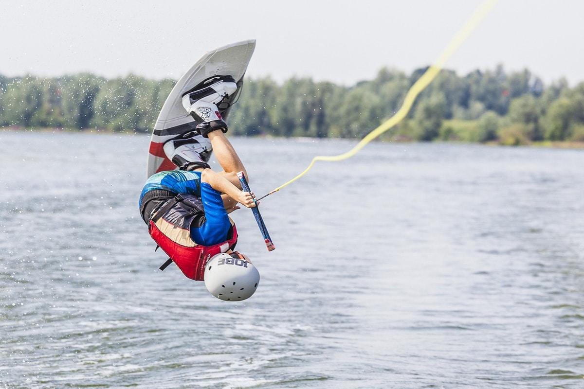 Wakeboarder die achter een boot op de Maas bij Ravenstein een salto maakt