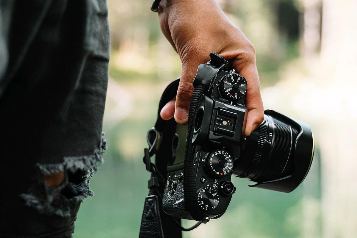 Een fotocamera die vast wordt gehouden in de linkerhand