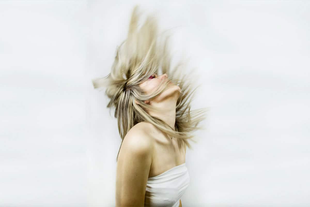 Jonge blonde vrouw gooit haar lange haren naar achteren en door de sluitertijd is de beweging van haar haren mooi vastgelegt