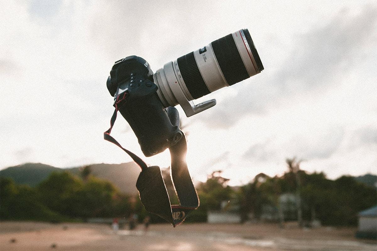 Canon fotocamera met een zoomlens die in de lucht gegooid is