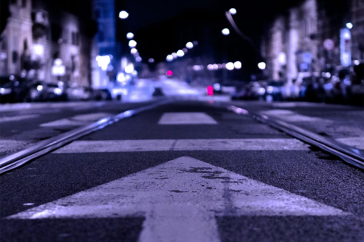 Een straat gefotografeerd in het donker met op de voorgrond een pijl en in de achtergrond de stad met verlichting