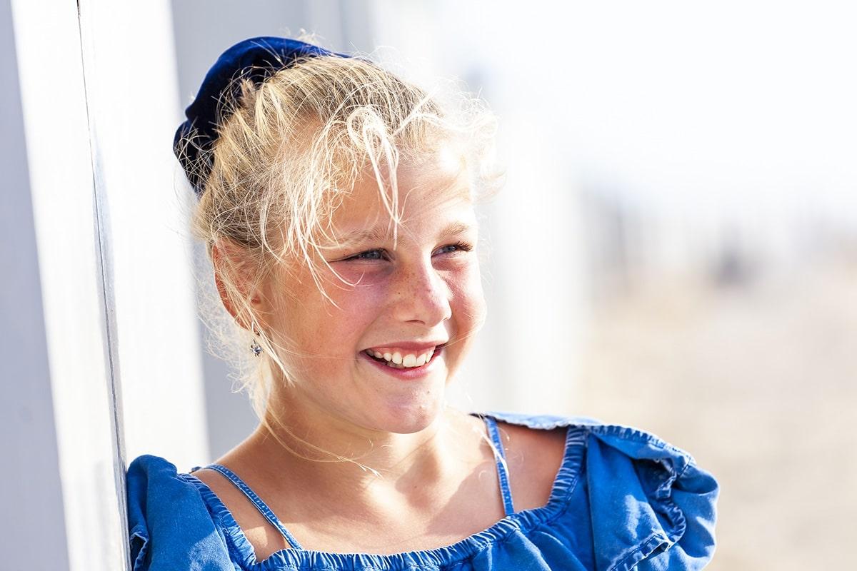 Vakantiefoto van een jong meisje op het strand leunend tegen een strandhutje