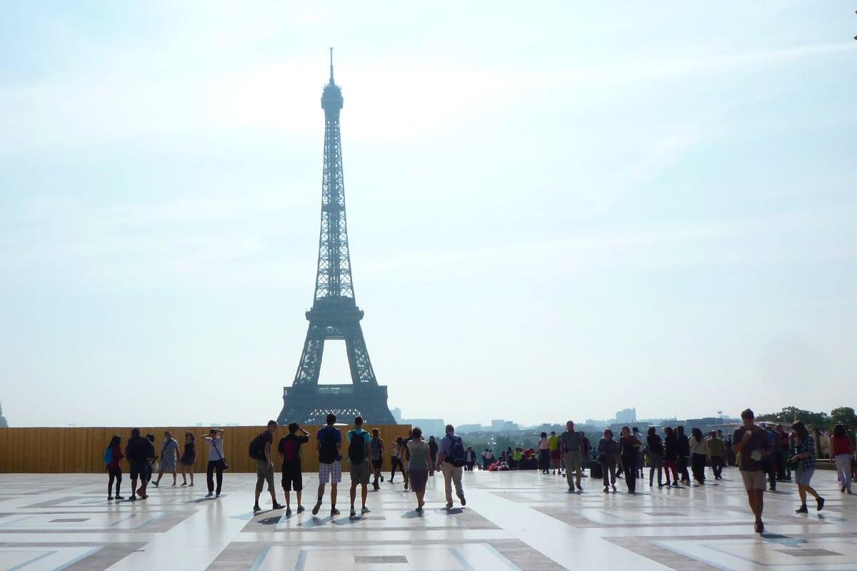 De Eiffeltoren in Parijs gefotografeerd met in de voorgrond allemaal mensen die naar de Eiffeltoren kijken