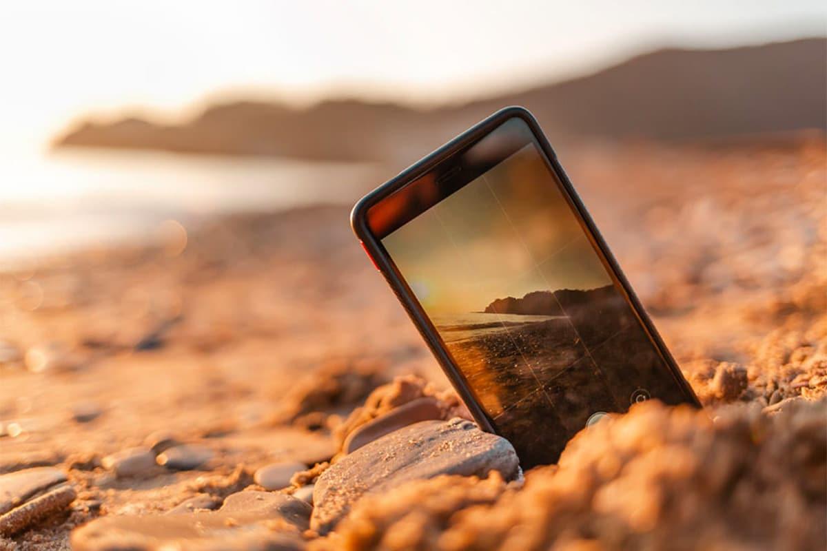iPhone in het zand op het strand die op het beeldscherm een zonsondergang laat zien