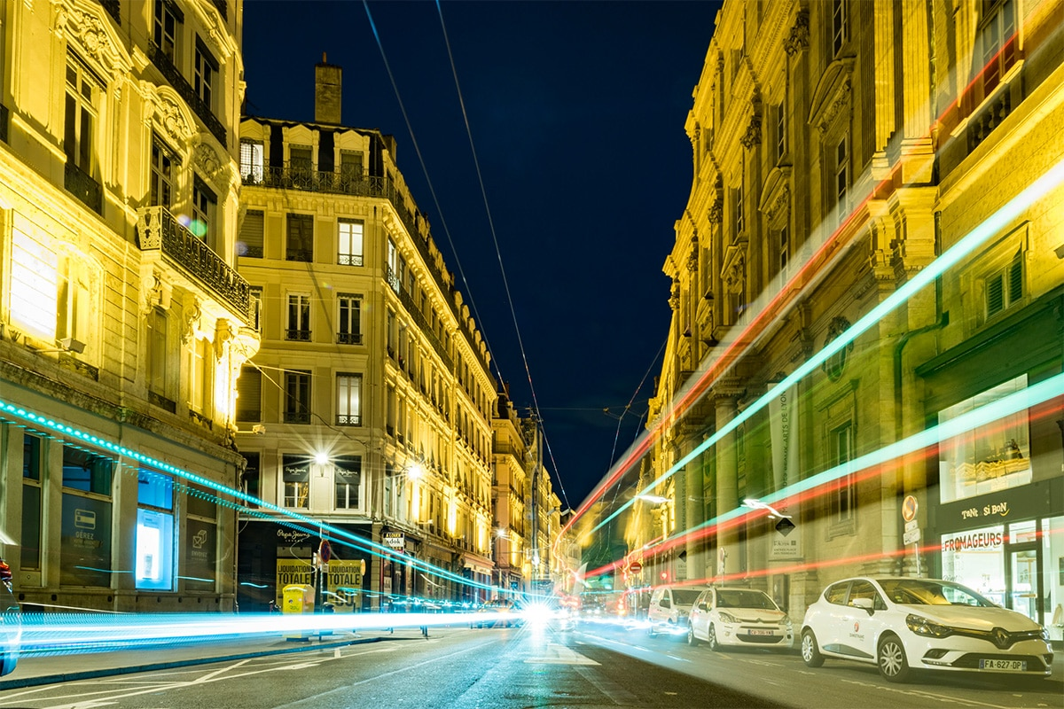 Een straat in Parijs gefotografeerd in het donker, waarbij de gebouwen verlicht en scherp zijn, en de auto's die door de straat rijden daar zie je alleen de verlichtingen van doordat de snelheid van de auto's snel zijn en de sluitertijd van de camera langzaam