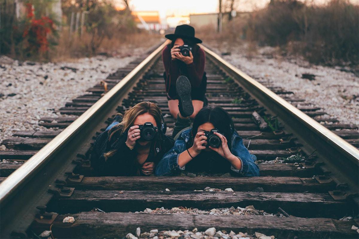drie vrouwen met een camera liggend op een treinrail, maken een foto van de fotograaf